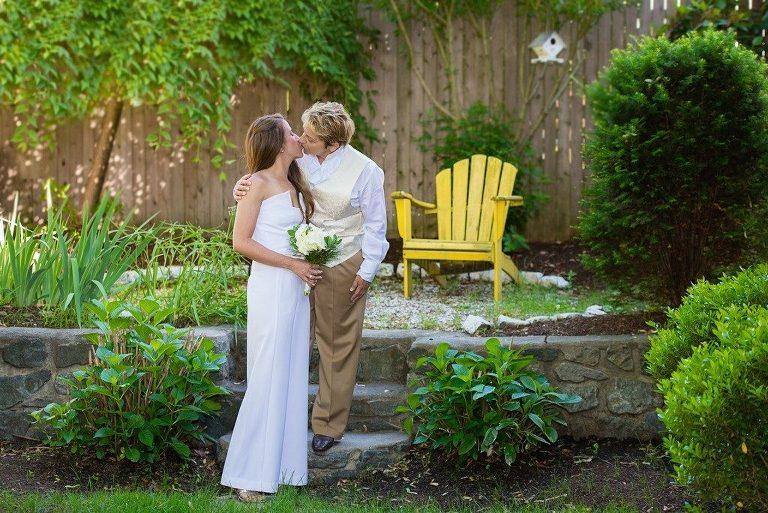 Happy wedding couple kissing on backyard