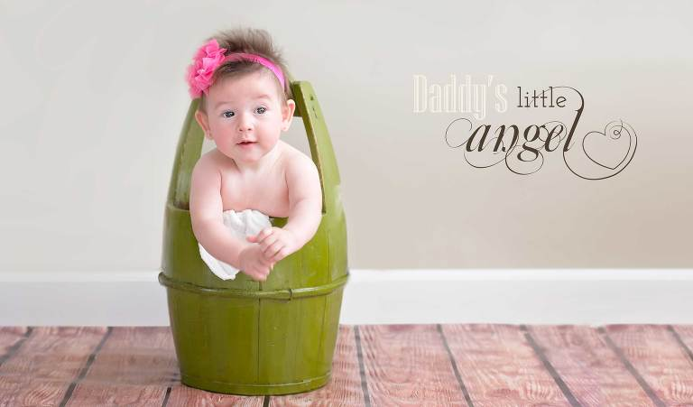 A baby girl inside a green bucket