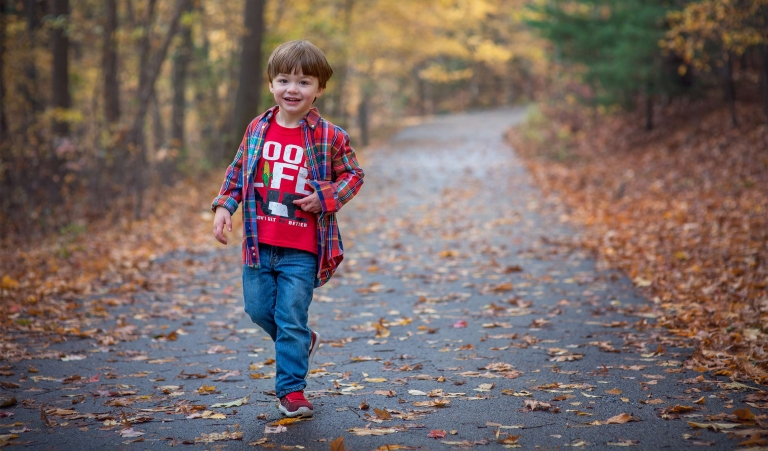 Toddler running on a trail on the fall season