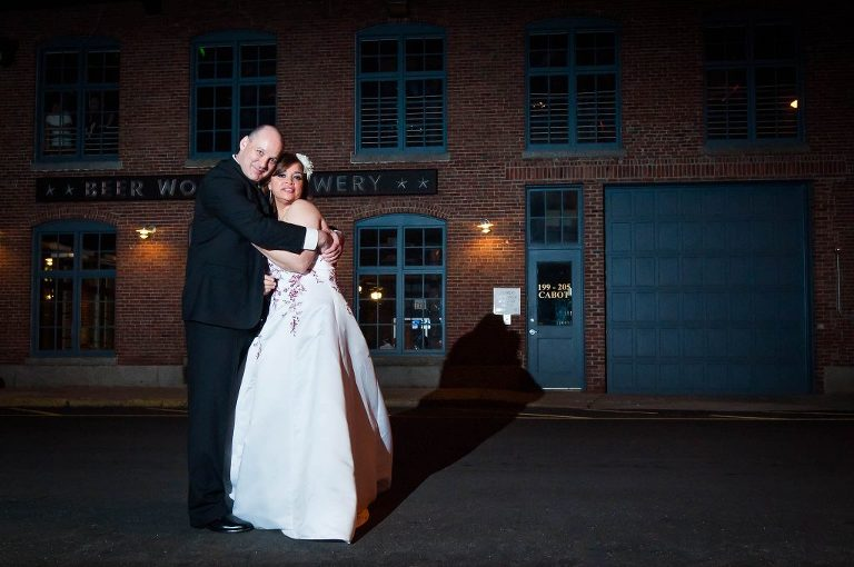 wed couple hugging outside Lowell Brewery