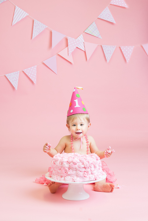 baby with pink cake