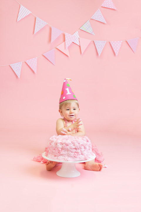 baby girl clapping hands with pink cake