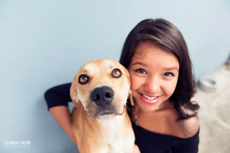 Teen in front of blue wall with dog posing for photo shoot