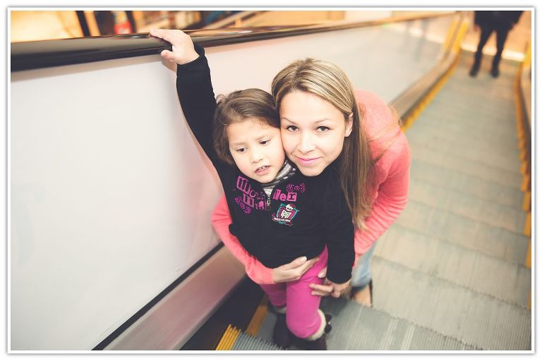 Mother and daughter going up on escalator at the mall