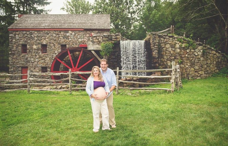 Pregnant couple posing in front of mill