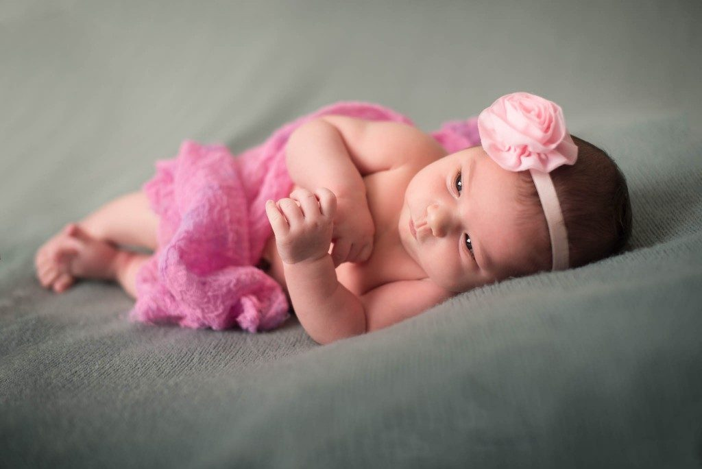 baby in pink laying down on bed