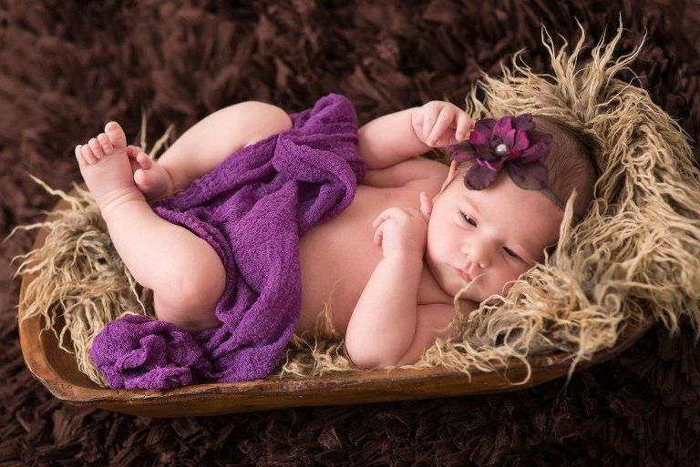 baby girl laying down in basket