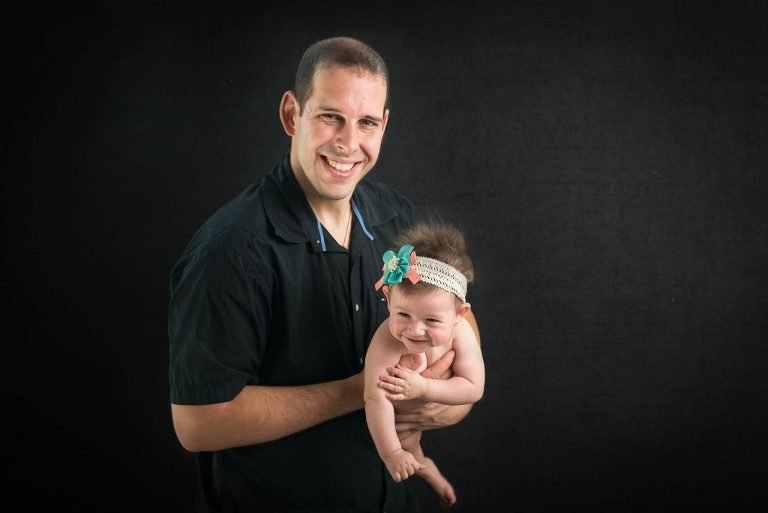 baby girl with father on black background