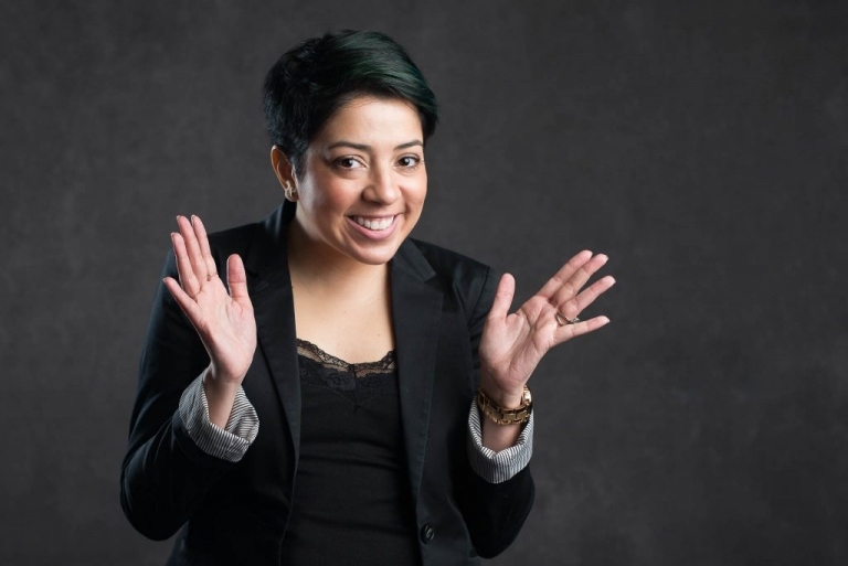 Young professional woman smiling with hand up