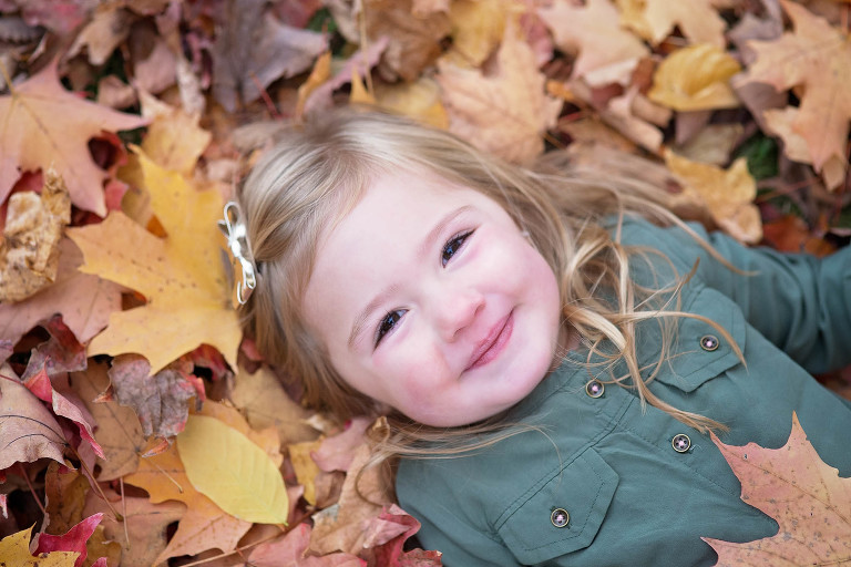 girl laying down on fall leaves