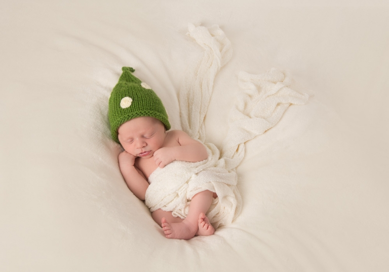 Newborn sleeping with green hat