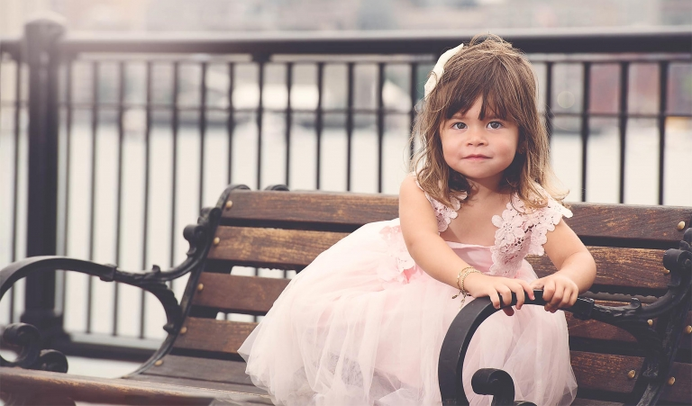Little girl in pink on a bench in East Boston