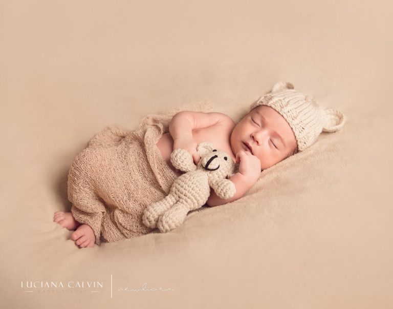 newborn sleeping with a little stuffed animal