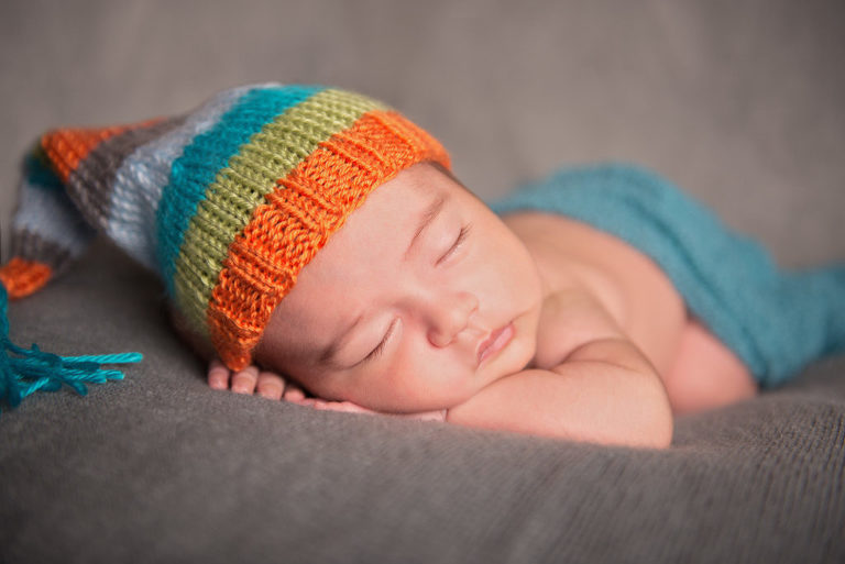 newborn baby sleeping with a colorful hat