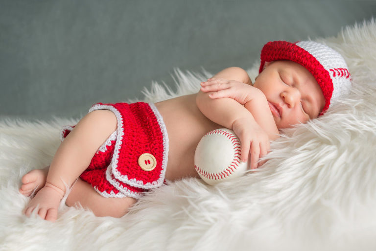 baby sleeping with baseball on white blanket