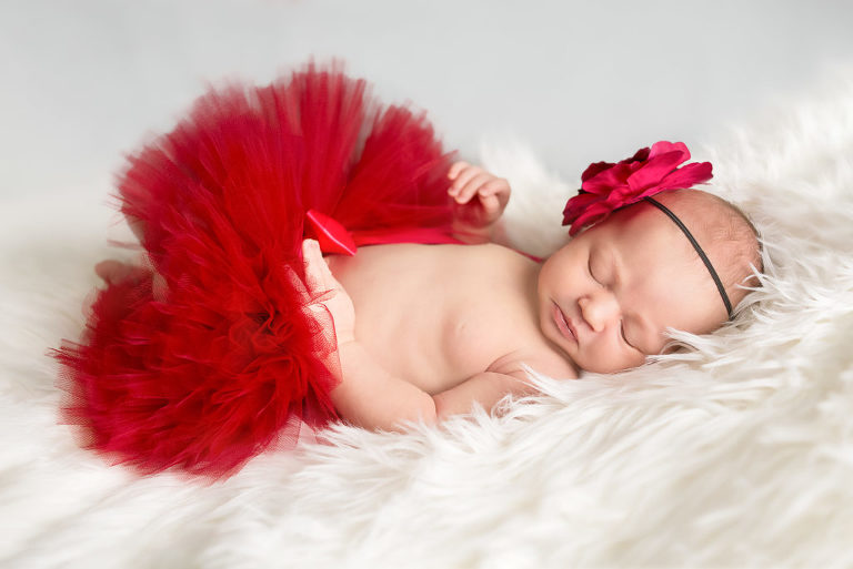 baby sleeping with red skirt
